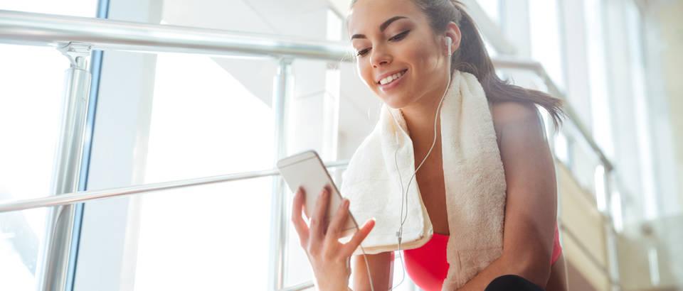 žena djevojka pametni telefon mobitel aplikacija glazba slušanje teretana shutterstock 390513577