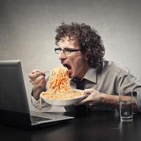 Jesti za radnim stolom računalo špagete apetit shutterstock 335742551