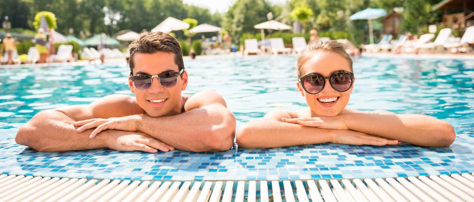 Bazen ljetovanje kupanje par ljubav dvoje žena muškarac sunce naočale shutterstock 311402252