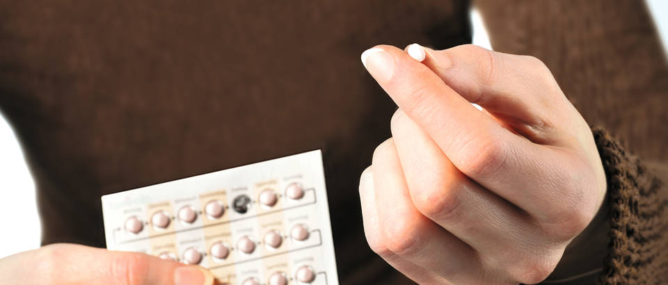 Woman holding contraceptive pill