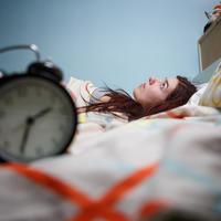 Nesanica spavanje žena krevet sat shutterstock 392337628