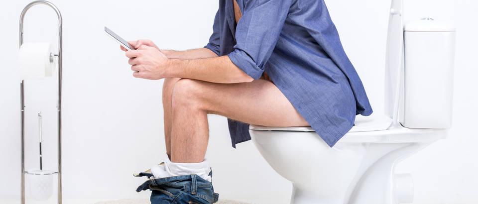 Zahod WC velika nužda probava crijeva mobitel muškarac shutterstock 234055573