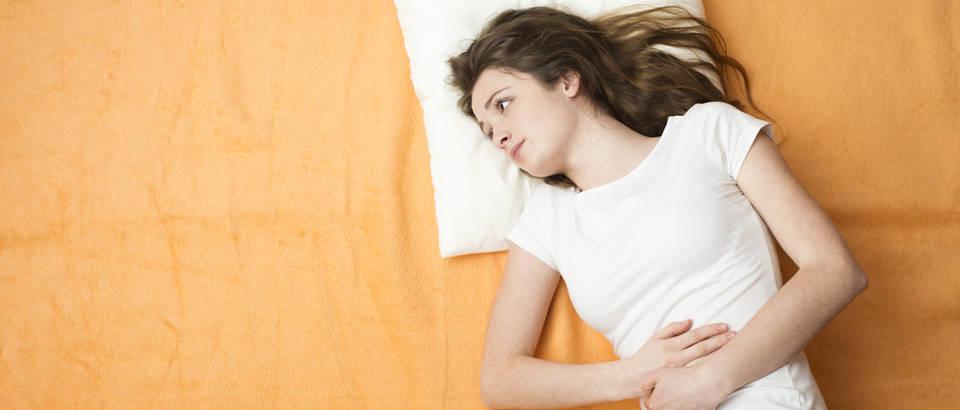 Trbuh mučnina djevojka žena krevet shutterstock 181003538
