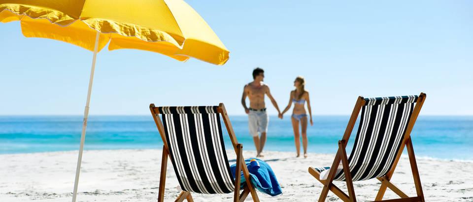 Ljeto plaza sunce suncobran lezaljka pijesak dvoje ljubav ljetovanje shutterstock 97744277